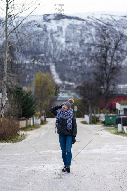 Female traveler in warm clothing and hat walking on empty road among trees with city on background at Tromso in Norway
