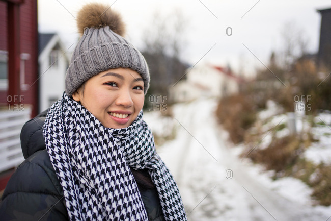 Cheerful Asian female traveler in warm clothing smiling and looking at camera with mountain on blurred background at Tromso in Norway