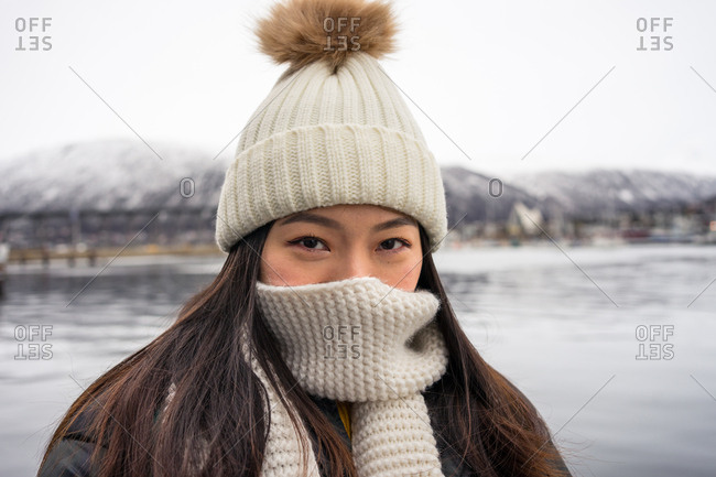 Young joyful Asian female tourist in warm clothing and hat smiling while sightseeing with mountains and sea on background at Tromso in Norway looking at camera