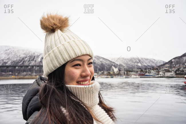 Young joyful Asian female tourist in warm clothing and hat smiling while sightseeing with mountains and sea on background at Tromso in Norway