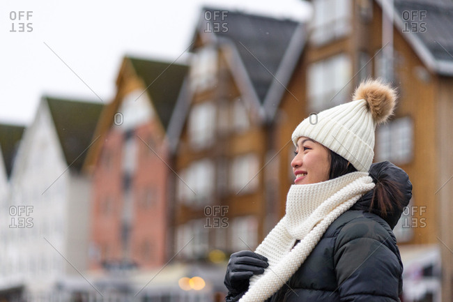From below side view of Asian pleased female on vacation in warm clothing smiling and looking away with modern building on blurred background in Tromso at Norway