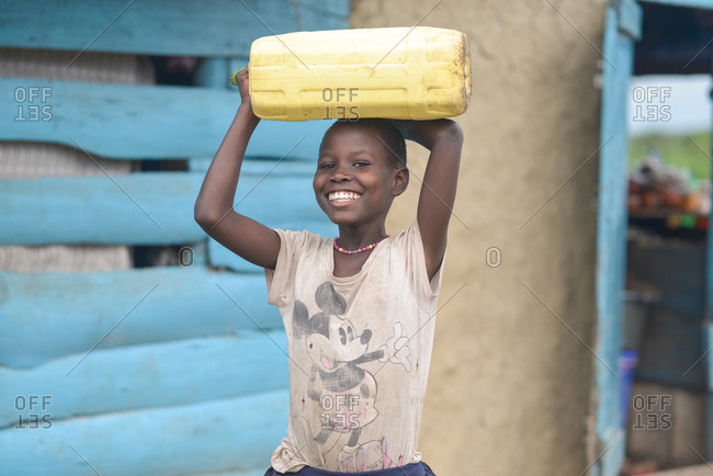 Uganda - November, 26 2016: Happy African girl smiling and looking at camera while carrying empty water canister with zucchini cork on head outside weathered house in village