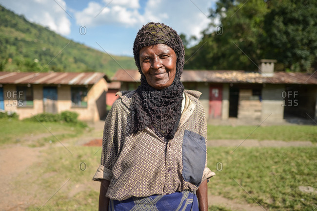 Uganda - November, 26 2016: Friendly mature black female in headscarf smiling and looking at camera while standing against houses on sunny day in village
