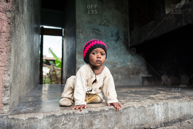 Uganda - November, 26 2016: Cute African baby in dirty pajama and knitted hat looking at camera while sitting inside uncompleted concrete building