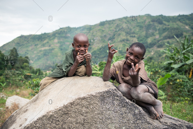 Uganda - November, 26 2016: African kids playing on a big rock with each other while looking at camera standing on green landscape