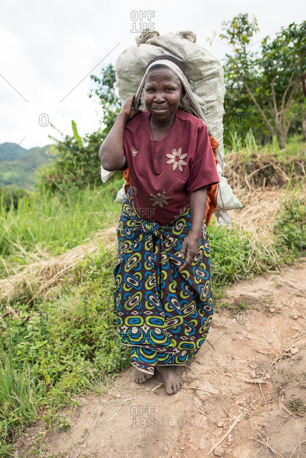Uganda - November, 26 2016: Full body senior African lady looking at camera and carrying sack on back while walking on path in forest