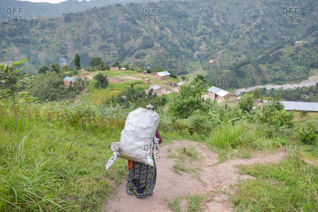 Uganda - November, 26 2016: Full body senior African lady looking away and carrying sack on back while walking on path in forest