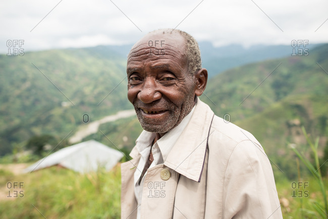 Uganda - November 26, 2016: Pensive senior African man in casual clothes looking at camera with kind gaze against amazing blurred scenery of green forested hills in daytime