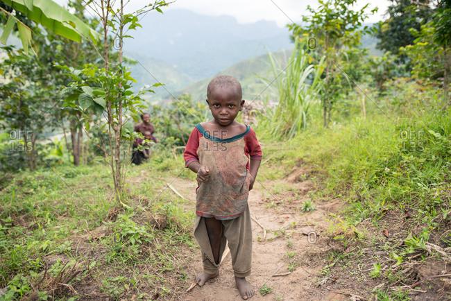 Uganda - November, 26 2016: Bald African toddler looking at camera while walking on dirty road outside village