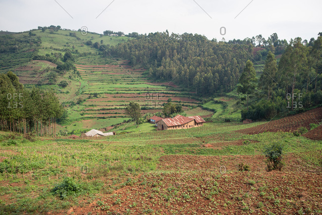 Uganda - November 26, 2016: From above magnificent scenery of countryside with small cultivated fields and solitary village among hills with green lush grass and dense forests