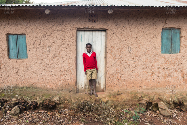 Uganda - November, 26 2016: African kid looking at camera while standing on weathered clay house door in a village