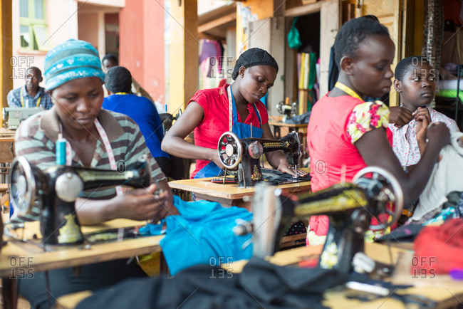 Uganda - November 26, 2016: Diligent African tailors in colorful clothes focusing and sewing garment using vintage foot sewing machine while working in local rustic workshop