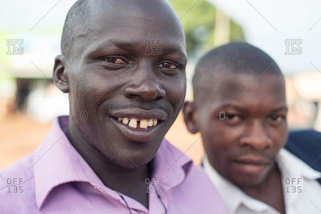 Uganda - November, 26 2016: Friendly young black men well dressed looking at camera while standing in the middle of a street in village