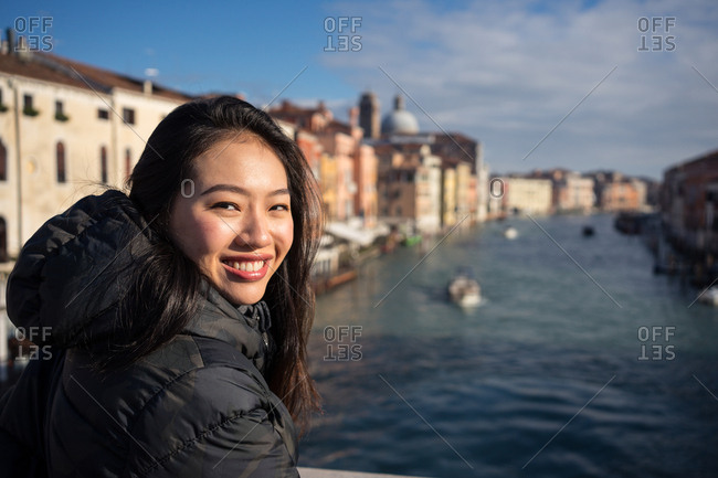 Asian female on vacation on ferryboat on waterline at city