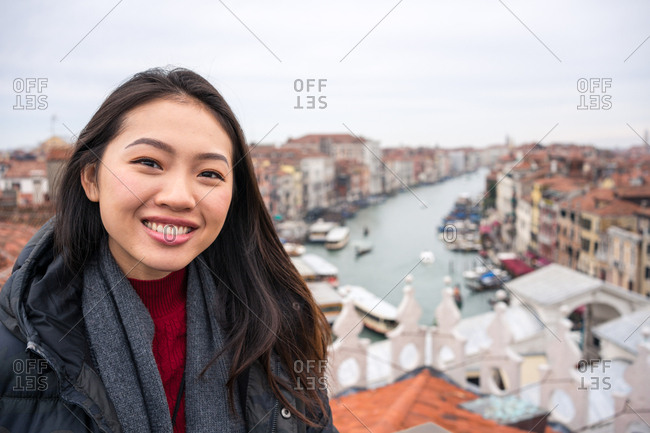Joyful Asian female traveler in warm clothing smiling and looking at camera with ancient city and waterways on blurred background on cloudy weather