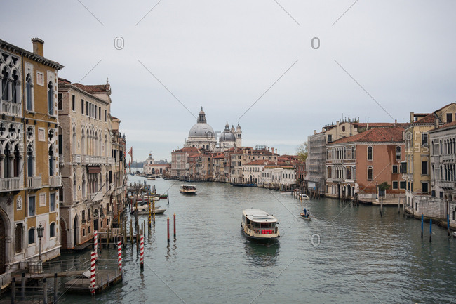 From above of waterline with ferryboats and gondolas among ancient beautiful buildings on cloudy weather