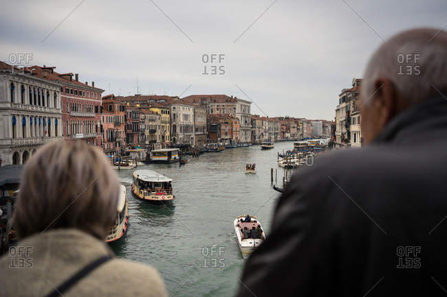Venice, Italy - November 16, 2019: Back view of faceless elderly male and female traveler in warm clothing standing and looking after water way with ferryboats