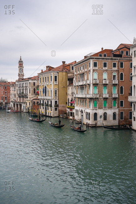Venice, Italy - November 16, 2019: Tranquil waterline with gondolas amid ancient beautiful buildings with cloudy sky on background