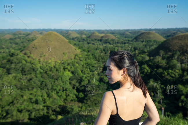 Back view of young Asian female tourist in black top and grey pants looking at camera standing next to fence on observation deck with green hills and blue sky in background