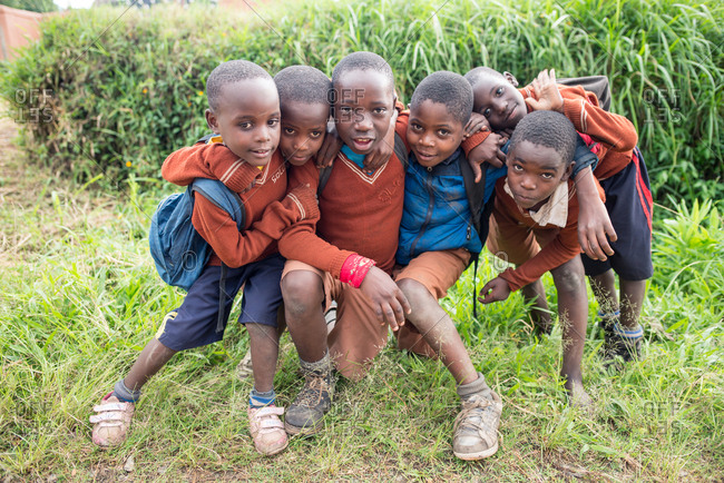 Uganda - November, 26 2016: African kids with school uniform hugging each other while looking at camera standing on green landscape