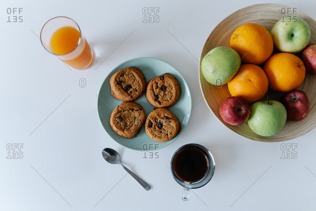 Top view of tasty cookies and glasses with beverages and plate of fruits on white table