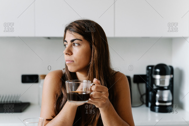 Thoughtful brown haired woman leaning elbow on table with cup of black coffee in hands and looking away at stylish kitchen