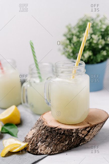 Taste lemonades in stylish tumblers with colorful plastic tubes serving on wooden slice and decorated squeezed lemons with nosegay on blurred background