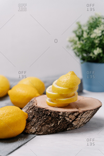 Side view closeup pieces of fresh lemons placed on wooden slice on blurred background
