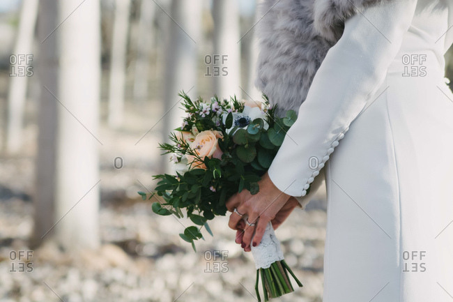 Side view of anonymous bride in white coat carrying bunch of flowers on blurred background of trees on sunny day