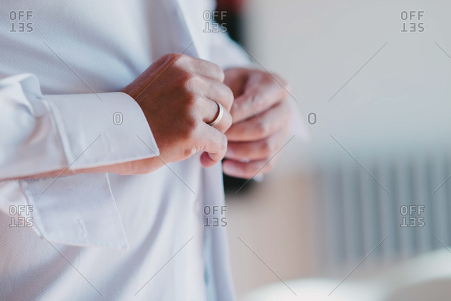 Unrecognizable groom with ring buttoning white shirt while preparing for wedding at home