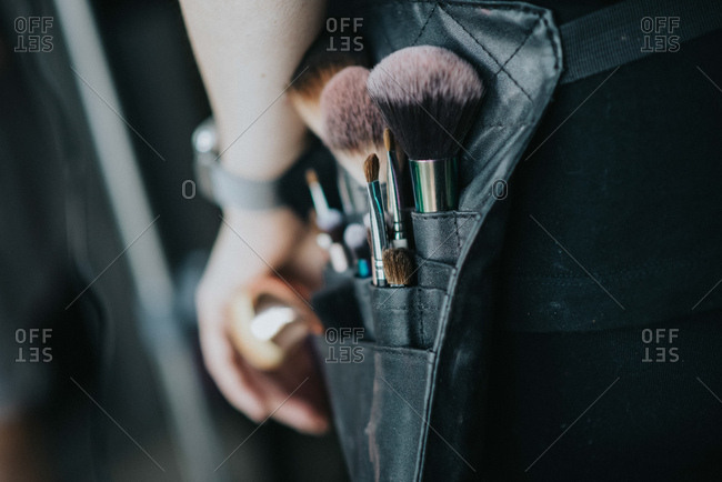 Unrecognizable person carrying bag with makeup brushes on waist during event preparation