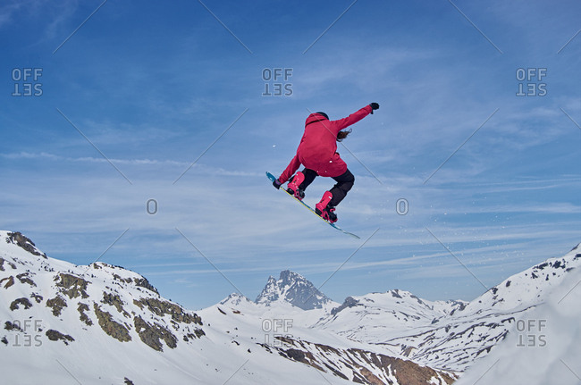 Unrecognizable snowboarder jumping on slope