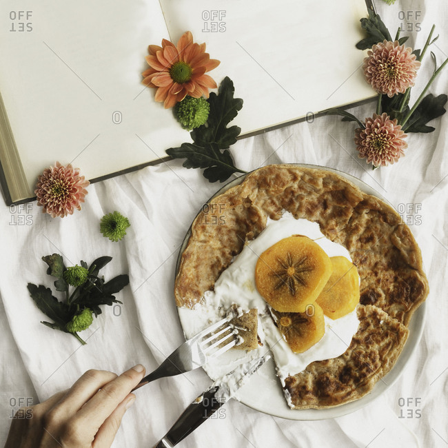 Top view of homemade crepes with cream and sliced persimmon served on plate with knife and fork on surface decorated with white cloth and flowers next to open book with empty pages