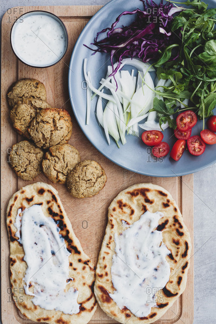 Top view of arrangement ingredients for cooking falafel and fresh vegetables and pita bread on cutting board