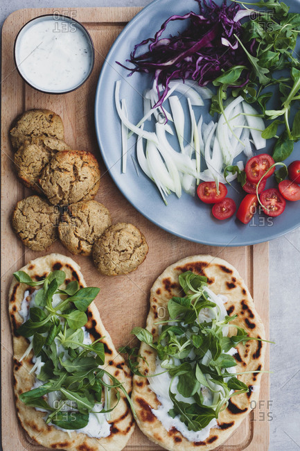 From above of food composition falafel and fresh vegetables on bread near with salad on cutting board