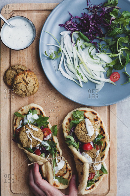 From above anonymous crop person hands on food composition falafel and fresh vegetables on bread near with salad on cutting board