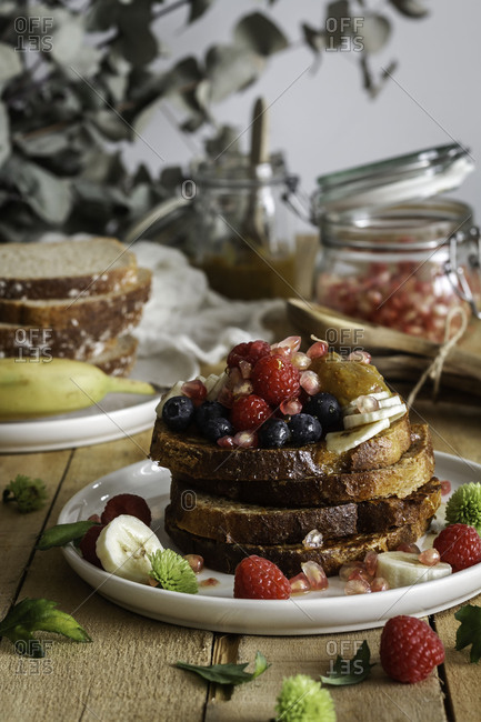 Honey pouring over fried toasts with fruit
