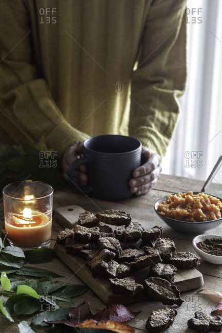Unrecognizable person in sweater warming hands with mug of hot beverage on table near fresh leaf shaped biscuits and candle at home