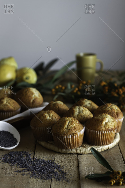 Appetizing fresh baked cupcakes on wicker stand on wooden table decorated with berries lemon and poppy seed for baking