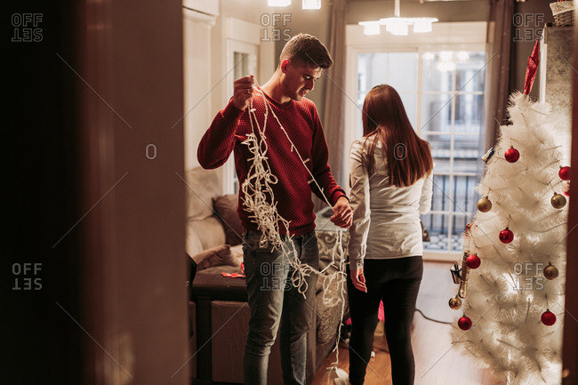 Young husband and wife decorating apartment and unwinding light garland while standing in living room with white Christmas tree decorated with red and gold balls