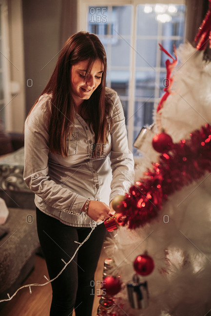 Side view of pregnant young woman decorating living room for Christmas and arranging white artificial Christmas tree