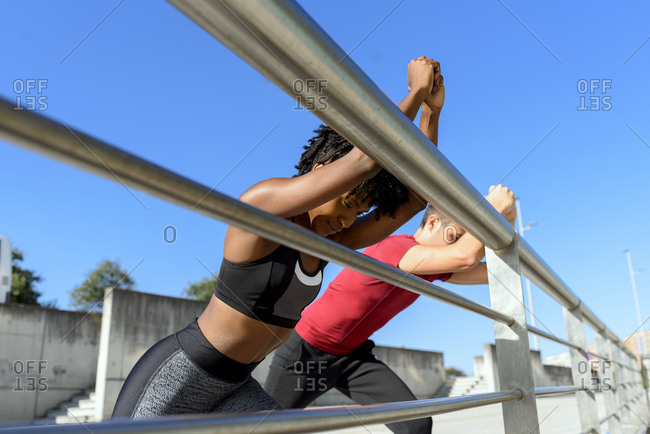 From below side view of cheerful African American fitness woman and smiling sportive man standing next to metal fence and stretching legs while training together on sunny day with blue sky in background