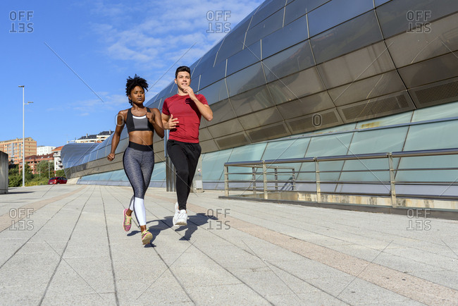 Young athletic African American female in top and leggings jogging with sportive male friend next to modern city construction in summer day
