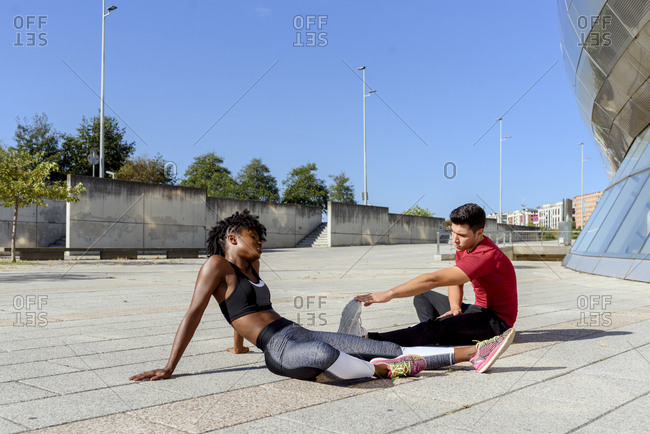 Side view of young African American woman in black sports top and leggings and man in red shirt sitting and stretching forward while practicing together in city in summer day