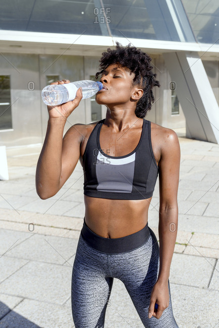 Young cheerful African American female runner in sports top and leggings standing next to building and drinking water while having break during training in city