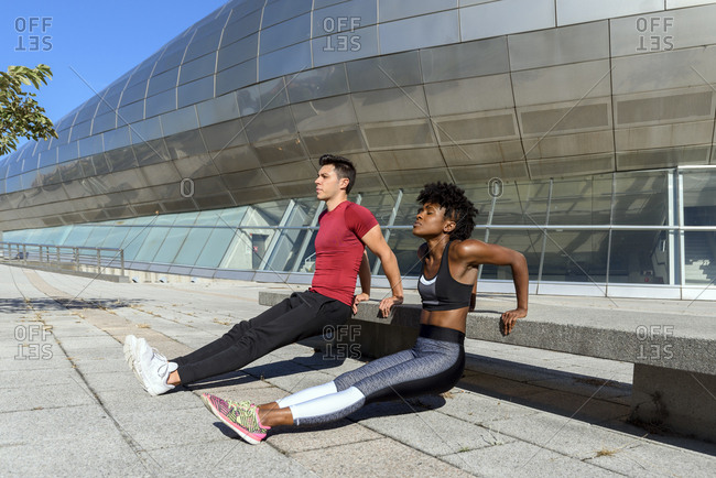 Side view of African American sportswoman in black sportswear and sportsman in red shirt doing push up exercises next to concrete bench in city