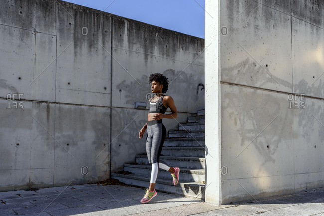 Athletic African American female in sports top and leggings running down stairs while training in sunny summer day in city with concrete wall in background