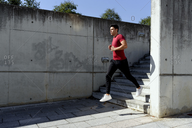Strong healthy active male in red shirt and black pants running down stairs during workout in sunny summer day in city with concrete wall in background