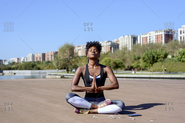 Modern African American sportswoman sitting in lotus pose and meditating after training at river bank in city in summer sunny day