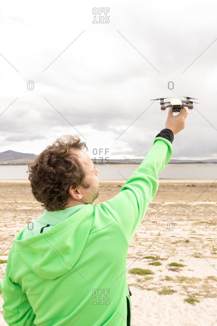 Back view of anonymous man lifting drone with camera from land using remote control panel in beach